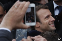 French independent centrist presidential candidate Emmanuel Macron shakes hands with well-wishers as he leaves the polling station after casting his ballot in the presidential runoff election in Le Touquet, France, May 7, 2017.