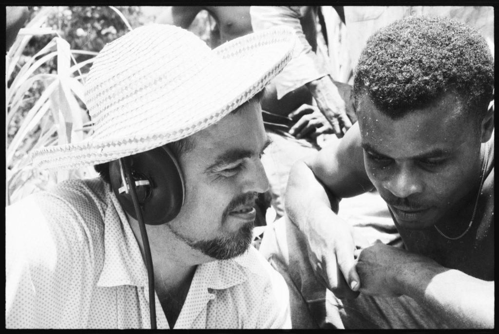 Closeup of the faces of Alan Lomax and Raphael Hurtault. Lomax wears headphones and a straw hat.