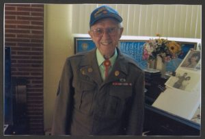 Benjamin Cooper wears his service uniform and a baseball cap and stands facing the camera.