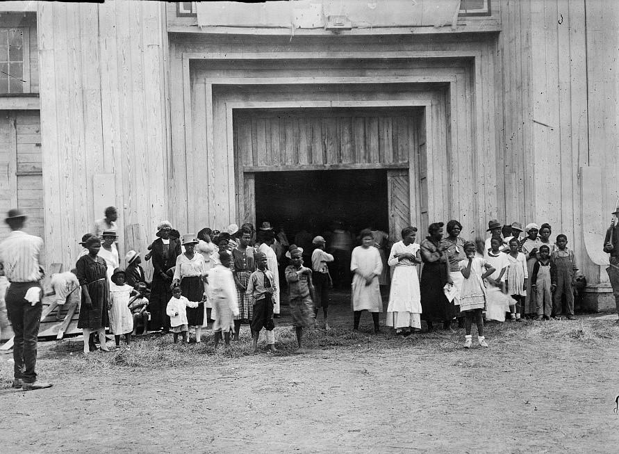 Black refugees huddled around entrance to fairgrounds