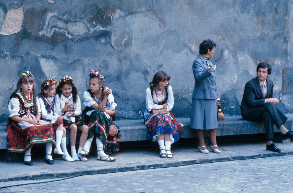 Five Polish school girls, in regional costumes, waiting next to a wall with two well-dressed adults. awaiting Pope John Paul's procession in Katowice, Poland., waiting for Pope