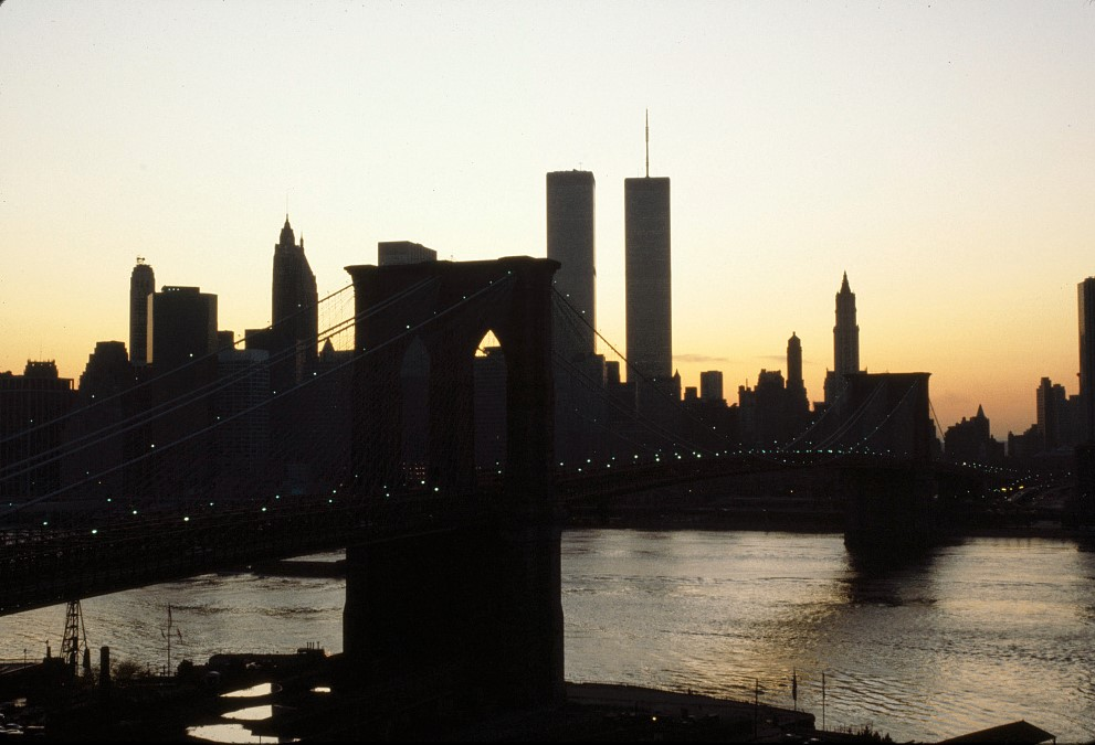 The sun has just set behind the New York City skyline, with the Brooklyn Bridge and Twin Towers at the center