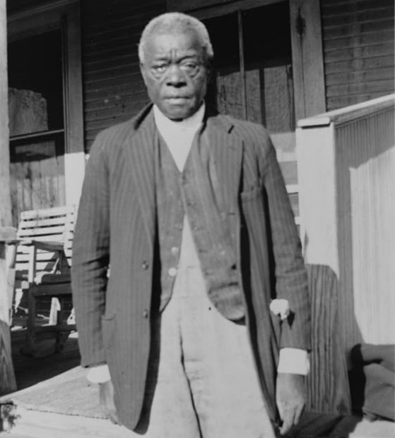 William Moore, with gray hair, wearing a suit coat, vest and slacks, stands by a front porch, looking at the camera.