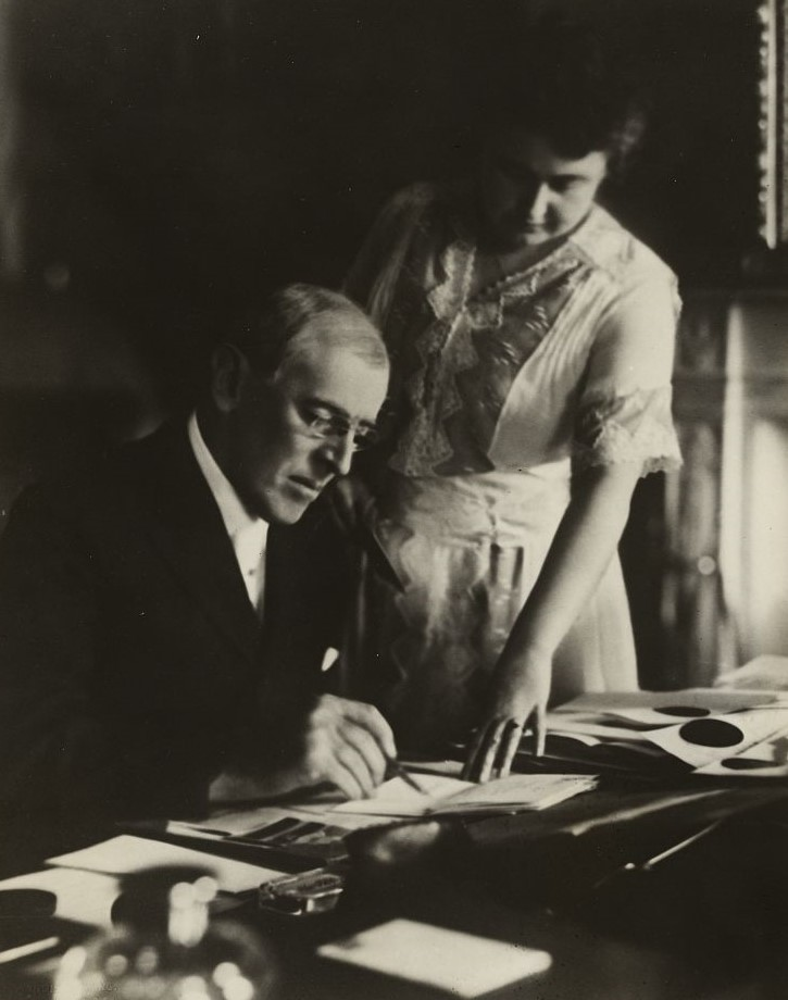 President Woodrow Wilson, seated at desk with his wife, Edith Bolling Galt, standing at his side
