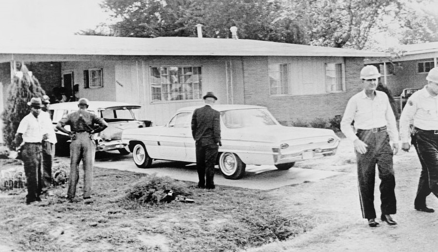 Medgar Evers house with two cars in driveway and several unidentified men, some white and some black, walking or standing.