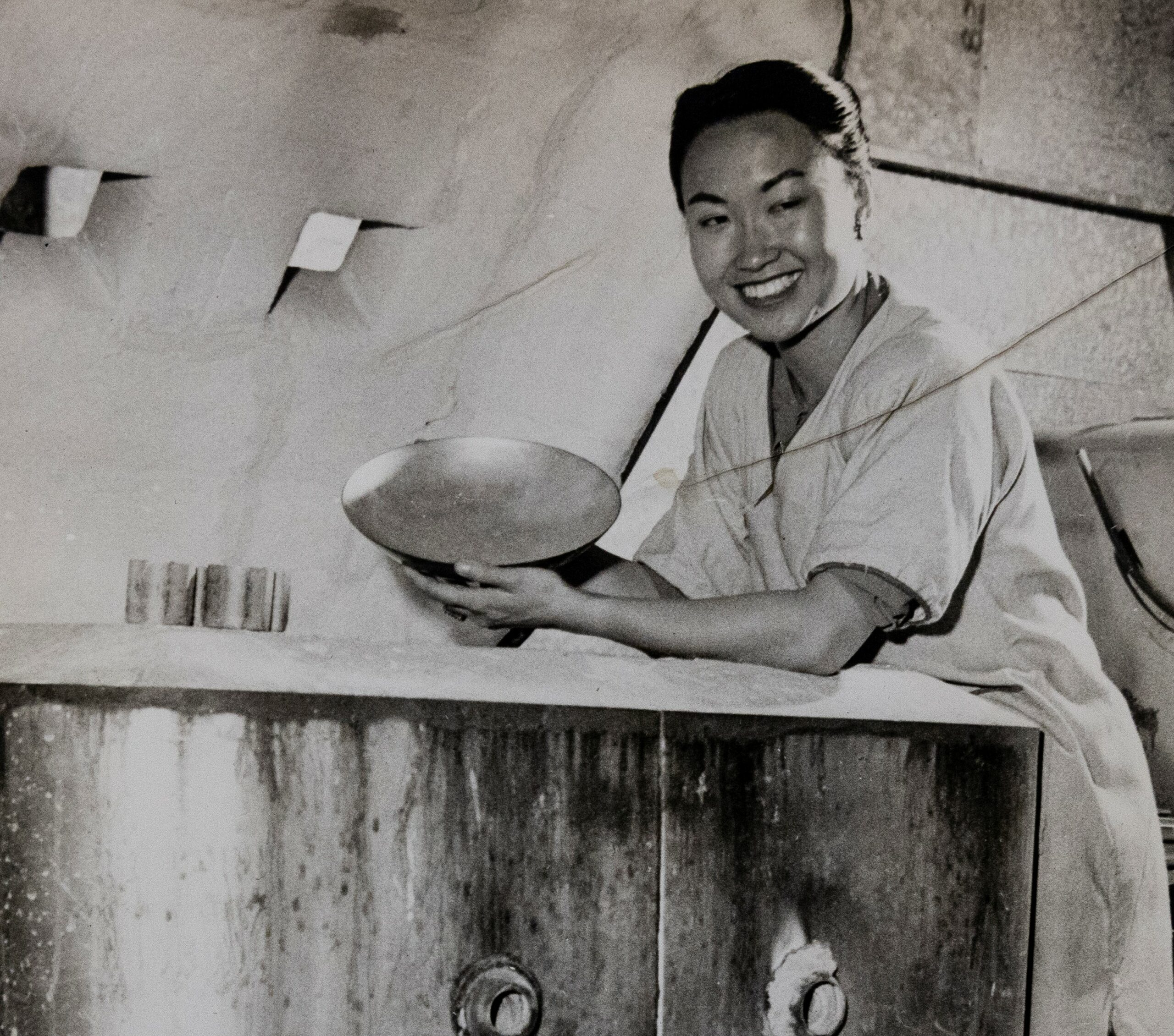 Jade Snow Wong, smiling, posed in her pottery workshop.