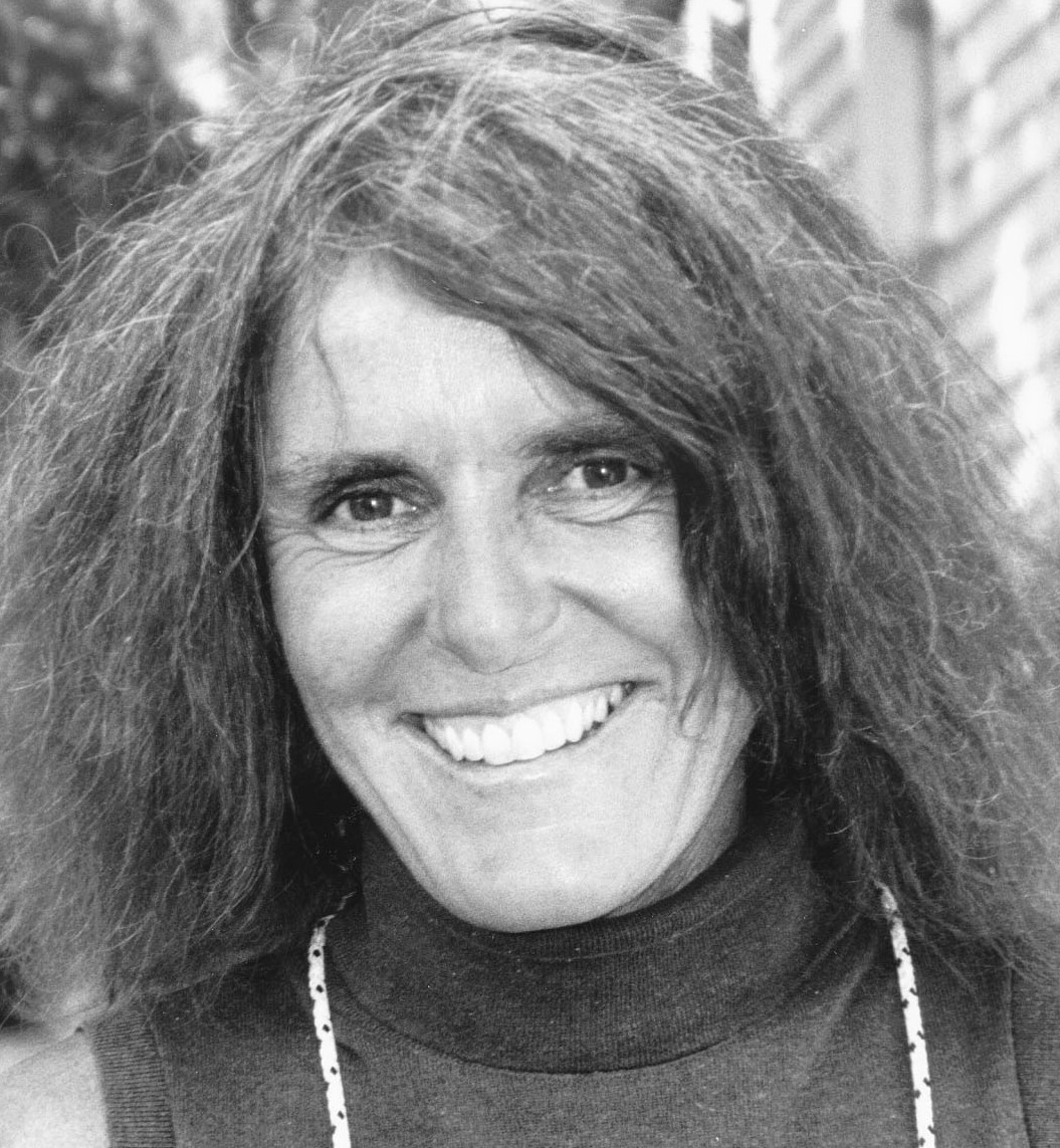 Headshot of Joy WIlliams, with a bright smile and long, loose hair, wearing a turtleneck sweater.