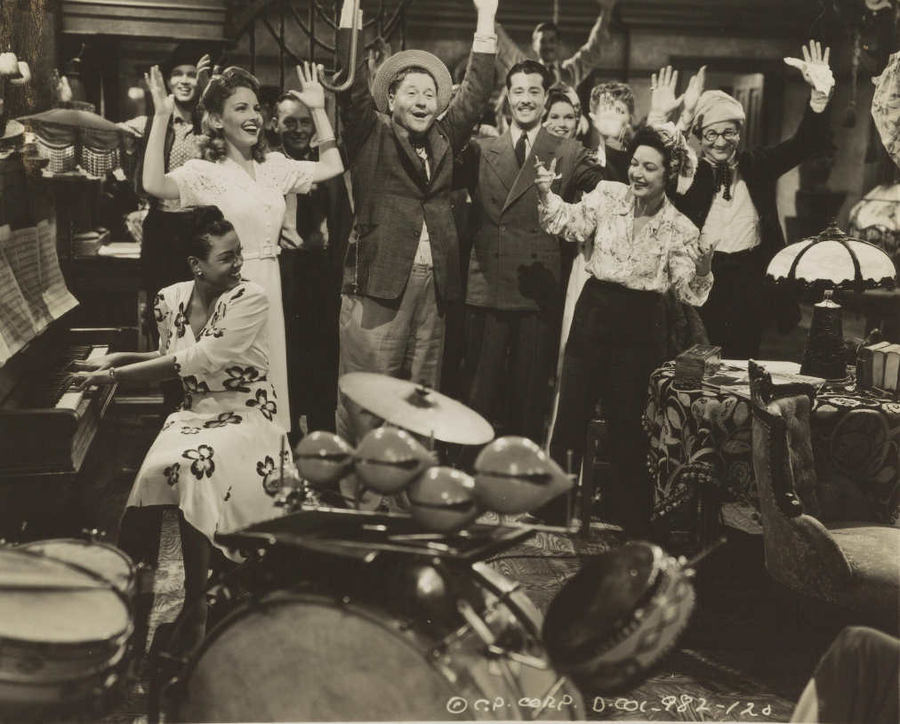 Scott, in a floral dress at piano, playing piano with a brilliant smile, turning to look at Red Skelton and other cast members, hands raised during a scene.